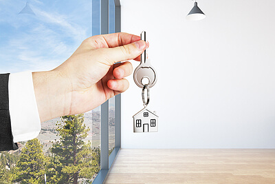 Photo of a man holding keys to a rental home.