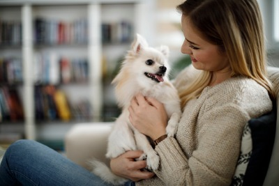 Picture of a woman relaxing at home with her dog.